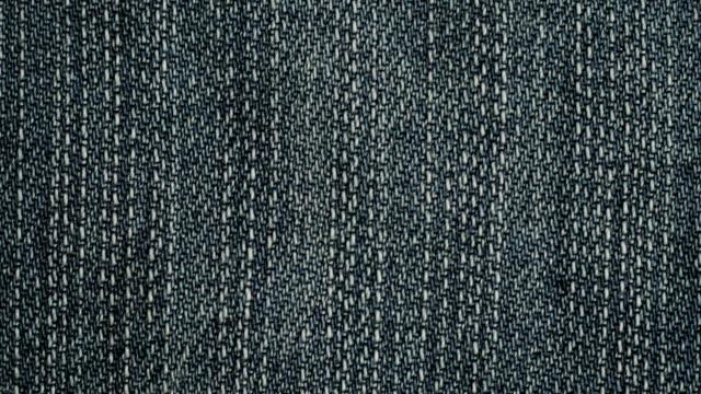 blue denim jeans texture. jeans background. top view. - dżinsy filmów i materiałów b-roll
