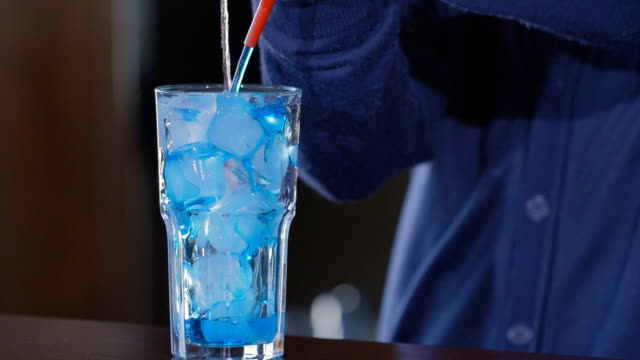 blue drink pours into glass. glass with ice and cocktail. exotic beverage at the bar. slow motion. - sussex occidentale video stock e b–roll