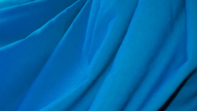 Blue fabric is fluttering in the wind.