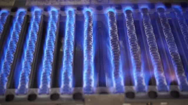 Blue flames of gas burner inside of boiler 4K Heating at home. Blue flames of gas burner being burning, closeup detail inside of boiler furnace. 4K ProRes HQ codec furnace stock videos & royalty-free footage