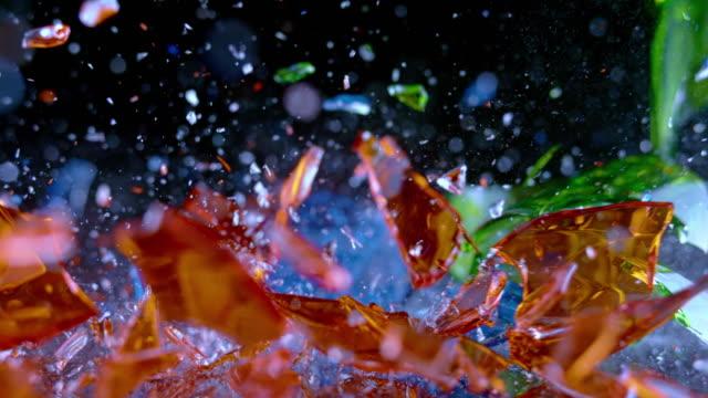 slo mo ldブルー、緑色とオレンジのクリスタルガラスが表面に当たって粉々に砕く - ガラス点の映像素材/bロール