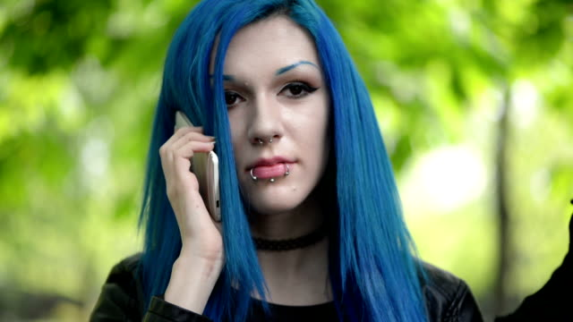 Blue haired girl using smartphone Blue haired girl using smartphone blue hair stock videos & royalty-free footage