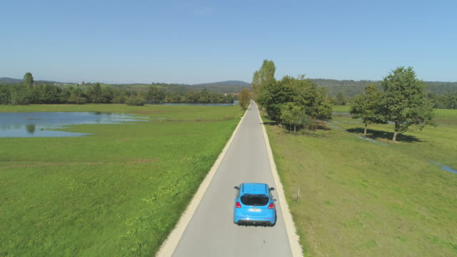 AERIAL Blue hatchback driving down a narrow road through submerged autumn nature video