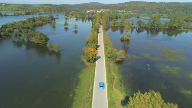 AERIAL Blue hatchback driving through flooded fields towards village on fall day video