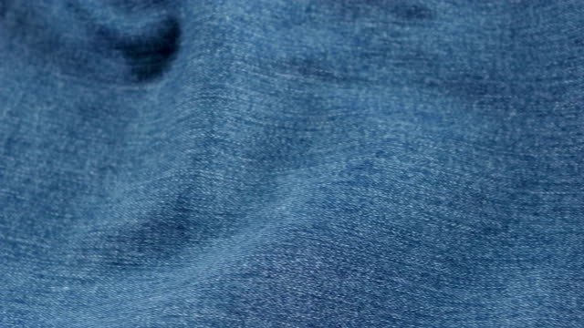 Blue jeans pocket on brown cloth, cam moves to the left, close up video