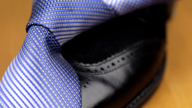 Blue knotted tie lies on a black men's shoes. Dolly shot. video