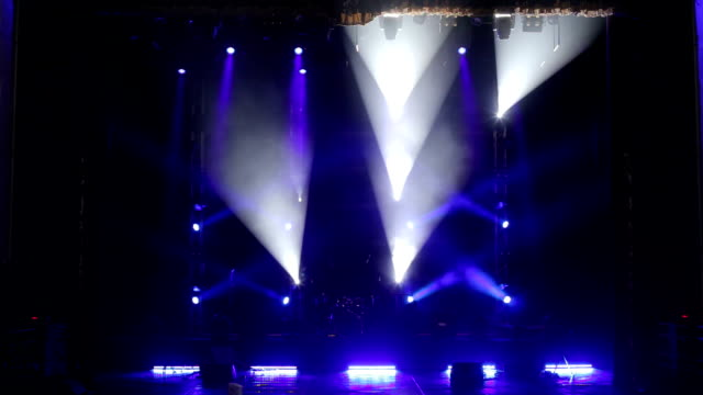 Blue light flashing and white rays on an empty stage in the dark.