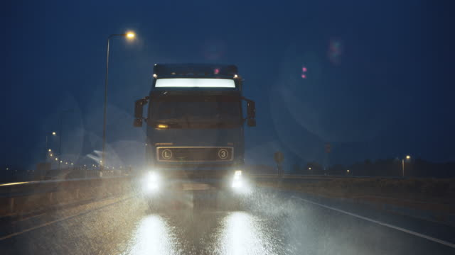 vídeos y material grabado en eventos de stock de semi-camión azul de larga distancia con remolque de carga lleno de mercancías viaja por la noche en la carretera de la autopista, conduciendo a través del continente a través de la lluvia, la niebla, la nieve. zona de almacenes industriales. disparo de - conductor de autobús