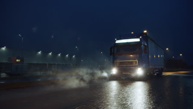 blue long haul semi-truck mit cargo trailer full of goods travels at night on the freeway road, driving across continent through rain, fog, snow. industrielagerbereich. front following shot - autotransporter stock-videos und b-roll-filmmaterial
