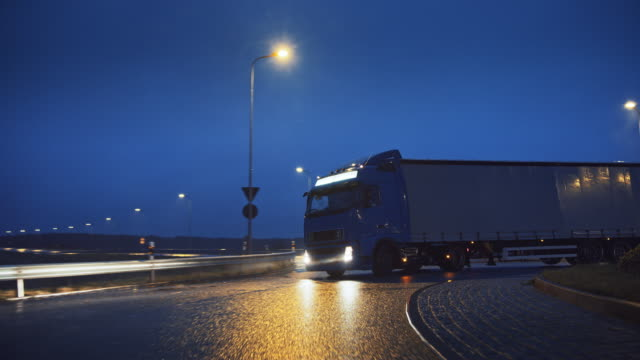 blue long haul semi-truck with cargo trailer full of goods travels at night on the freeway road, driving across continent through rain, fog, snow. industrial warehouses area. front following shot - fare la lotta video stock e b–roll