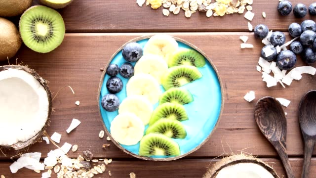 stockvideo's en b-roll-footage met blauwe majik, spirulina superfood smoothie kokosnoot bowl roteren - tropisch fruit