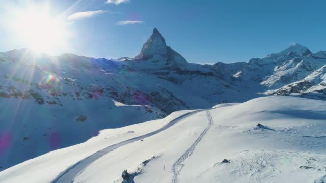 stockvideo's en b-roll-footage met blauwe matterhorn mountain in zonnige winter dag. zwitserse alpen. zwitserland. luchtfoto. blauwe hemel - matterhorn