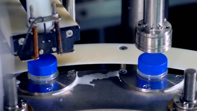Blue milk bottle caps are twisted by a factory machine. video