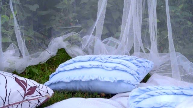 Blue pillows and white transparent fabric at park. Beautiful wedding decor Blue pillows and white transparent fabric at park. Beautiful wedding decor. White veil decorations. Fashion decorative pillows and blanket. Delicate transparent decoration tulle netting stock videos & royalty-free footage
