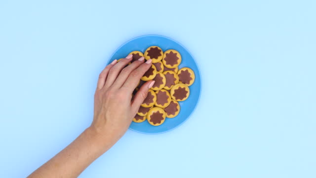 Blue plate with cookies appear on blue theme and hand take one cookie. Stop motion
