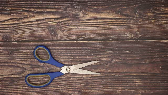 blue scissors on wooden background - stop motion - forbici video stock e b–roll