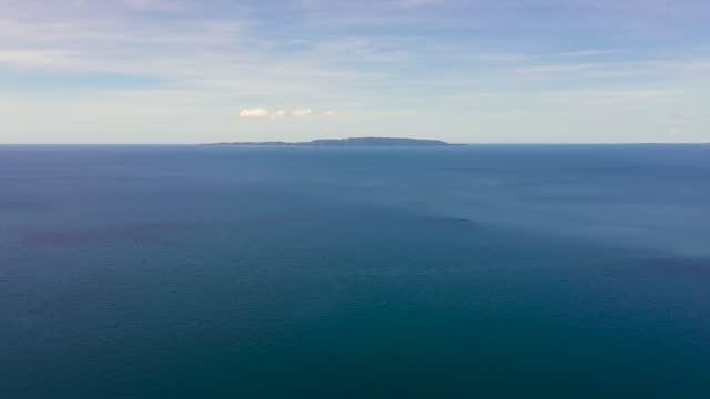 mare blu e isola tropicale limasawa. filippine - baia video stock e b–roll