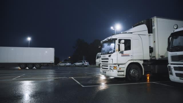 貨物トレーラーを備えた青いセミトラックは、他のトラックが立っている一晩駐車スペースにドライブします。一晩駐車場で夜休むドライバー - トラック点の映像素材/bロール
