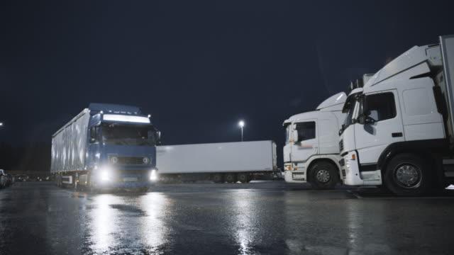 貨物トレーラー付きブルーセミトラックは、他のトラックが立っている一晩の駐車スペースからオフドライブします。ロングホールトラックは、大陸全体の貨物/商品を輸送し、駐車場を残し - トラック点の映像素材/bロール