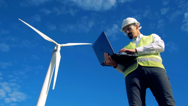 Blue sky with a turbine tower getting controlled by an engineer with a laptop