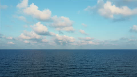 Blue sky with white clouds moving panorama summer. Sea in light of day aerial view of drone slide forward. Small waves on sea. Sunny sunset over the sea. Sun way. Horizon Blue sky with white clouds moving panorama summer. Sea in light of day aerial view of drone slide forward. Small waves on sea. Sunny sunset over the sea. Sun way. Horizon clear sky stock videos & royalty-free footage