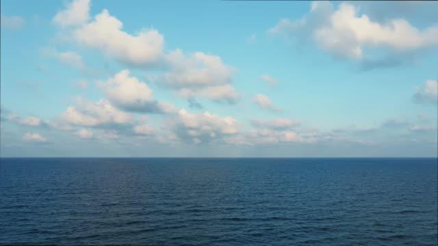 vídeos de stock e filmes b-roll de blue sky with white clouds moving panorama summer. sea in light of day aerial view of drone slide forward. small waves on sea. sunny sunset over the sea. sun way. horizon - linha do horizonte sobre água