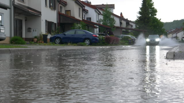 LOW ANGLE Blue SUV drives through the flooded streets of a suburban neighborhood