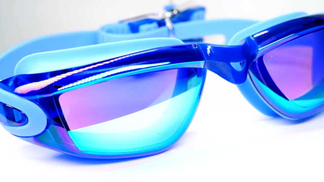 blue swimming goggles rotating on white - vídeo