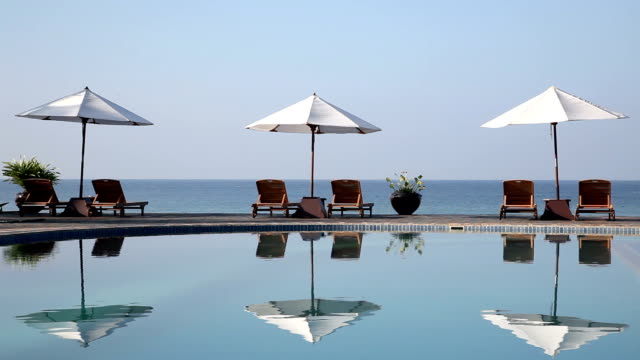 blue swimming pool with umbrellas against sky and ocean video