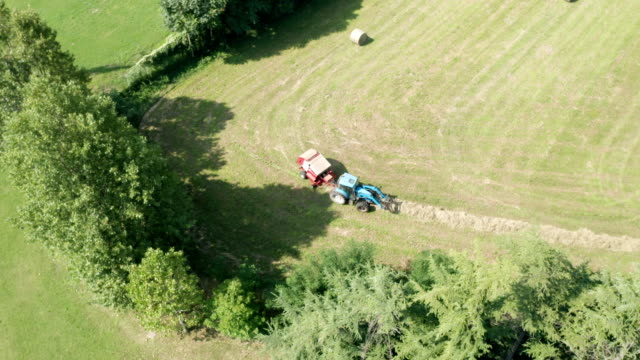 Blue Tractor Hay Bales Trees Aerial View