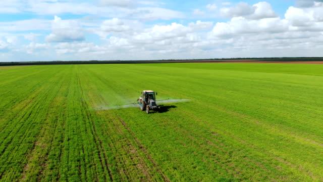 Blå traktor sprutvete fält med kemikalier i molnigt vårdag video