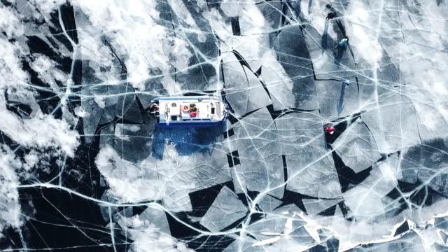 vídeos de stock e filmes b-roll de blue transparent ice field lake baikal. picturesque deep cracks frozen snow. cinematic ship boat an air cushion rides. russia north. tourist attraction. winter sunny. aerial drone top high - lago baikal