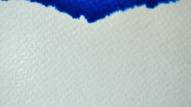 Blue watercolor is flowing and spreading on the white paper