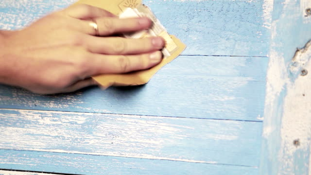 A blue wooden background is being polished with sandpaper