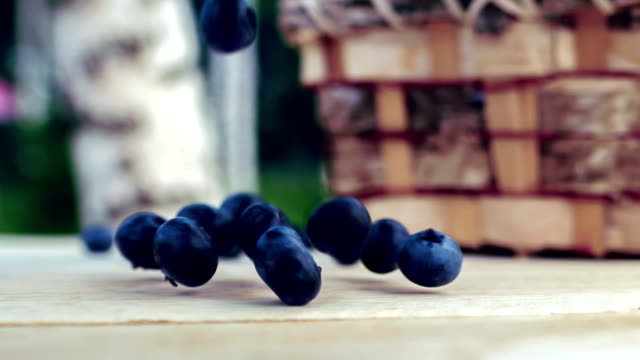 Blueberries fall on a wooden table video
