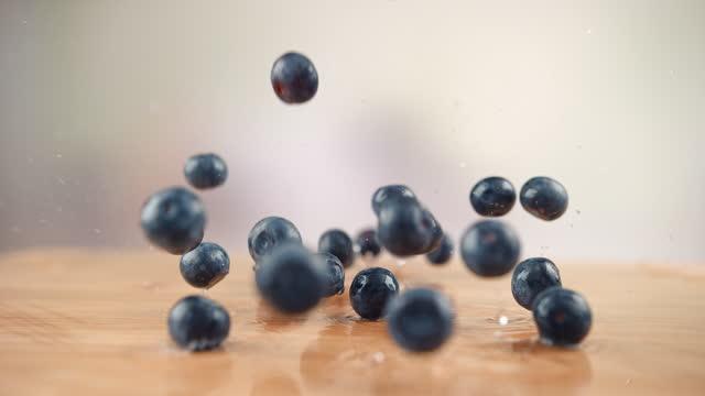 vidéos et rushes de les bleuets tombent sur la table en bois et éclaboussent les gouttes d'eau autour dans 1000fps - baie eau