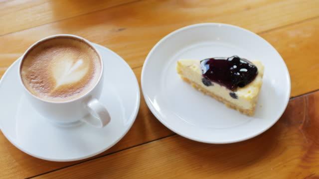 tarte au fromage aux bleuets avec du café latte art sur une table en bois pour le concept de détente, coup de dolly - Vidéo