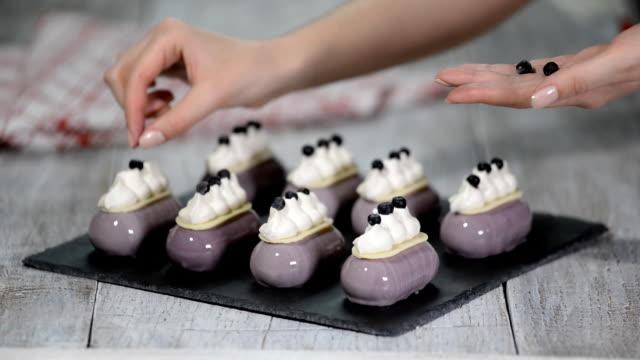 vídeos y material grabado en eventos de stock de pastel de mousse de arándanos cubierto con arándanos y crema batida en la panadería shop. - suflé