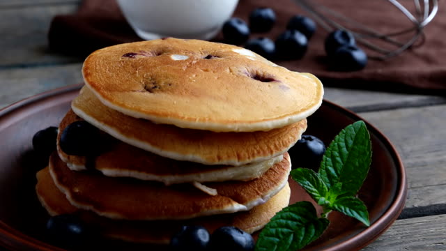blueberry pancakes on a plate pour maple syrup - pancake video stock e b–roll