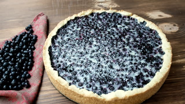 Blueberry pie sprinkle with powdered sugar , on the wood table Blueberry pie sprinkle with powdered sugar , on the wood table, close up painting art product stock videos & royalty-free footage