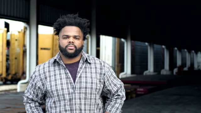 Blue-collar worker at train loading dock A young African-American man in his 20s, a blue-collar worker with a thick beard, staring at the camera with a tough, no nonsense expression. Then he crosses his arms over his chest. He is standing by a railway loading dock. manual worker stock videos & royalty-free footage