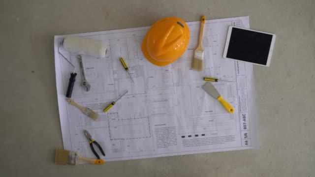 blueprint på golv med olika verktyg en tablett och hjälm på toppen - construction workwear floor bildbanksvideor och videomaterial från bakom kulisserna