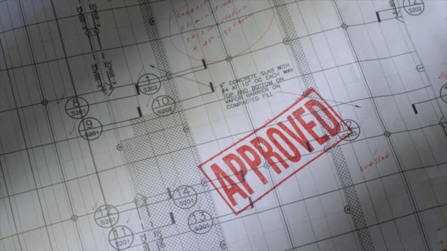 Blueprint with APPROVED Rubber Stamped Blueprint with the word APPROVED stamped in red representing stock videos & royalty-free footage