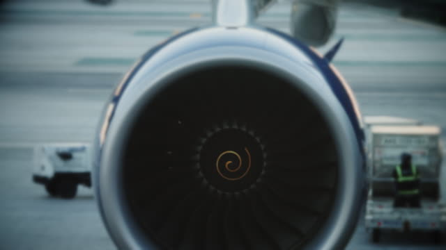 Blue-toned Jet Turbine Clip focused on the spinning turbine on the wing of a large airplane, with vehicles, staff and equipment of the ground crew visible in the background. turbine stock videos & royalty-free footage