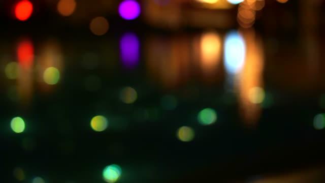 vídeos de stock, filmes e b-roll de blur luz bonita de piscina noite estrelada, iluminar a fibra óptica de luz ao lado do restaurante - foco no primeiro plano