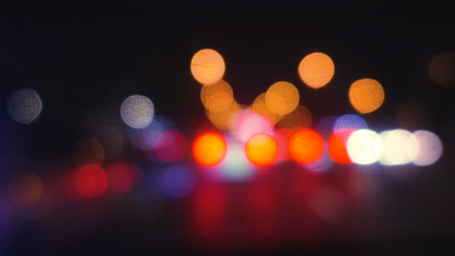 blur bokeh light at road while car is driving on street at night with colorful bokeh background