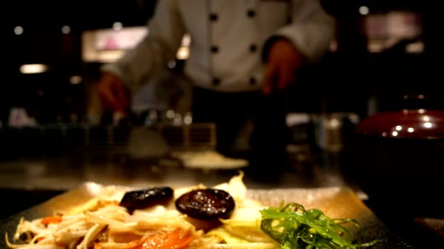 blur bokeh restaurant with chef cooking frying something on background - busy restaurant kitchen stock videos & royalty-free footage