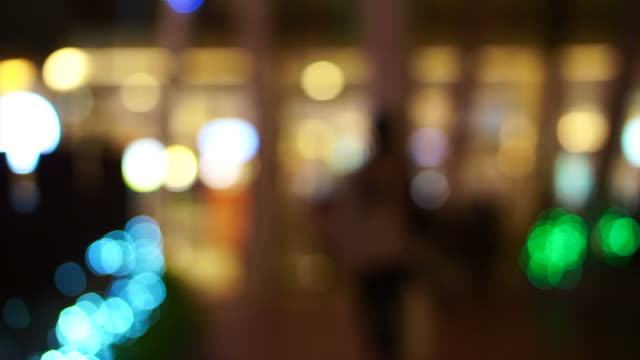 Blur holiday light bokeh background with people shadow walking video