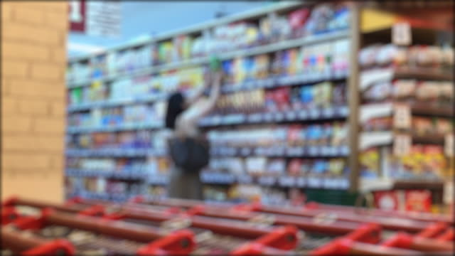 Blured woman pick up goods on shelf in shopping store The foreground is red cart represent supermarket and people walking with basket and shopping snack aisle stock videos & royalty-free footage