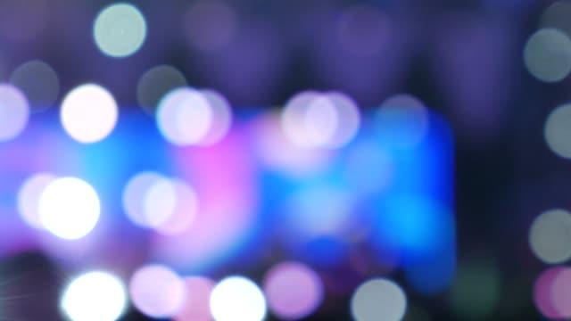 suddig bakgrund av färgade lampor från scenen på en levande musikfestival på natten. - nattliv bildbanksvideor och videomaterial från bakom kulisserna